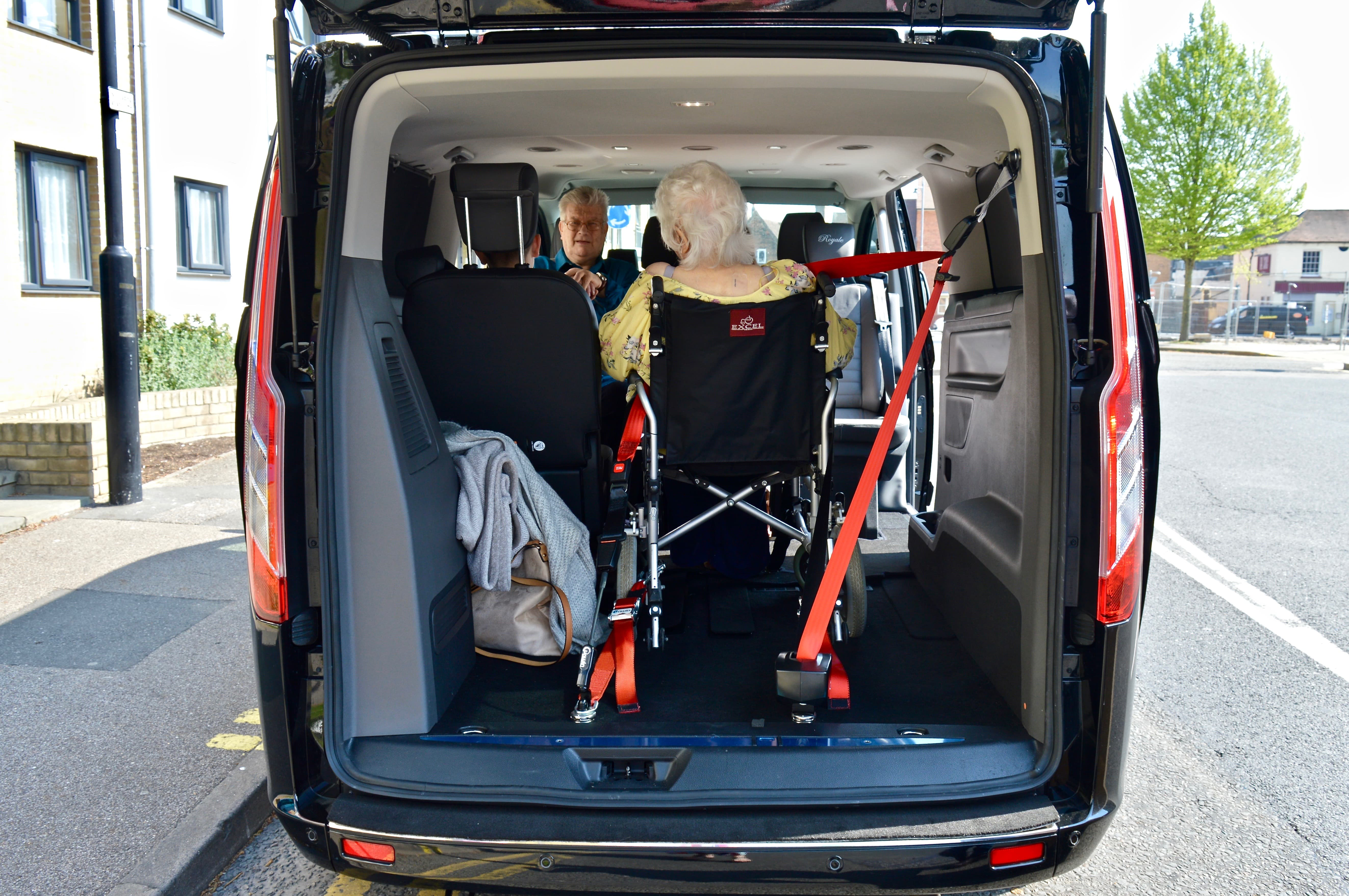 Rear end of vehicle showing wheelchair user secured into taxi