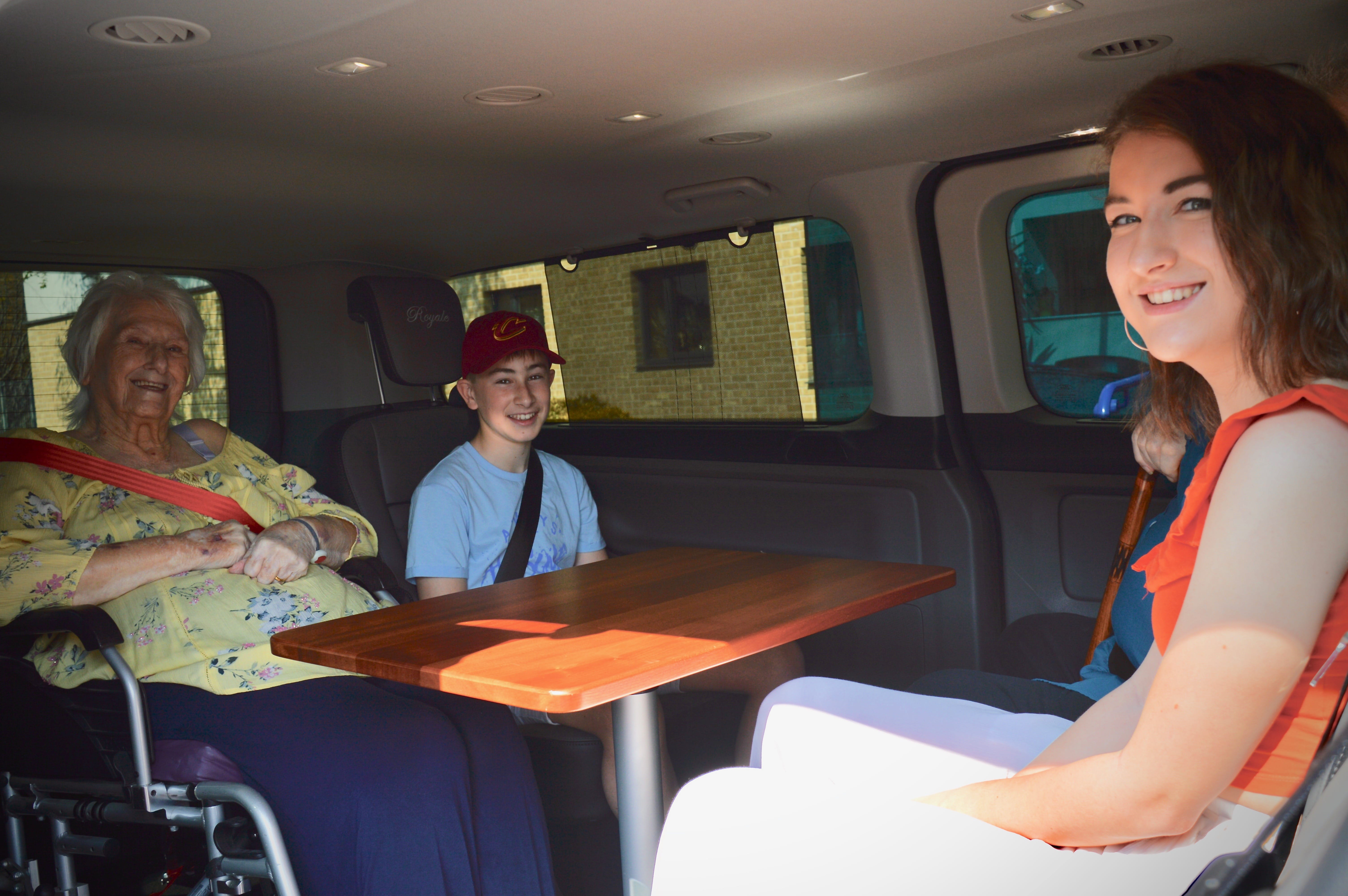 Pasengers sitting with wheelchair user within vehicle around table