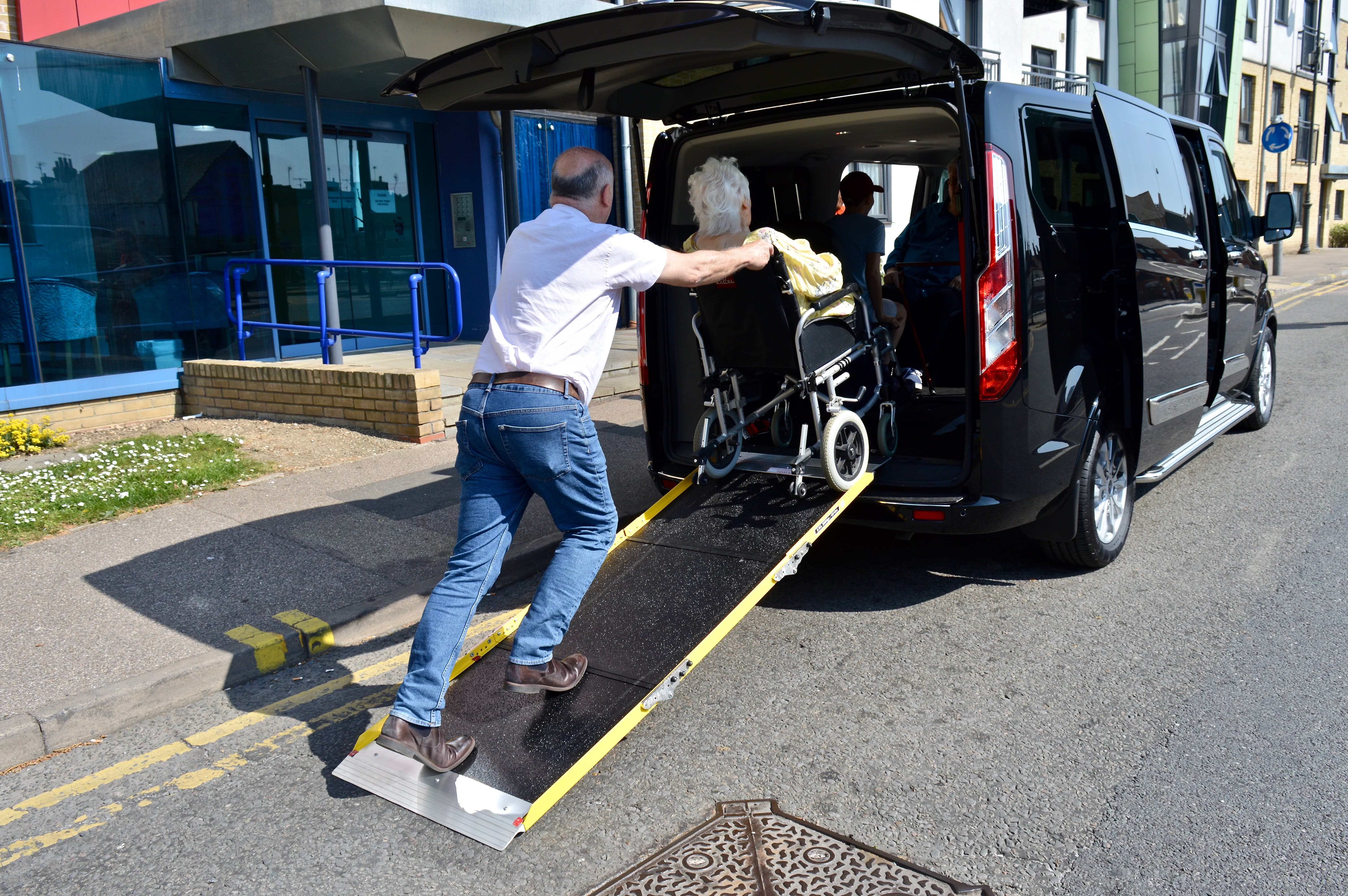 Wheelchair user being pushed up a ramp into wheelchair accessible taxi