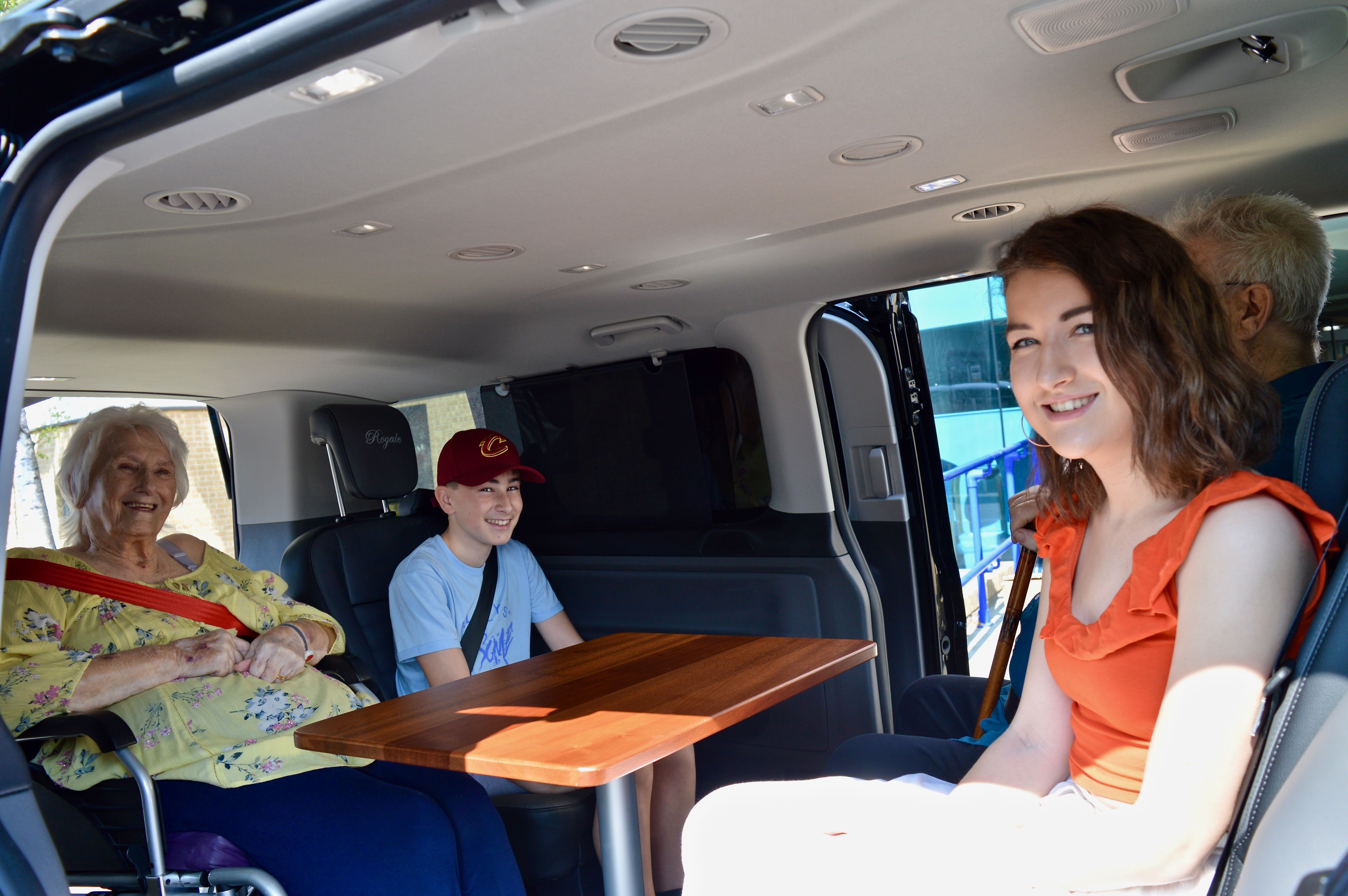 Wheelchair user sitting with family within wheelchair accessible vehicle